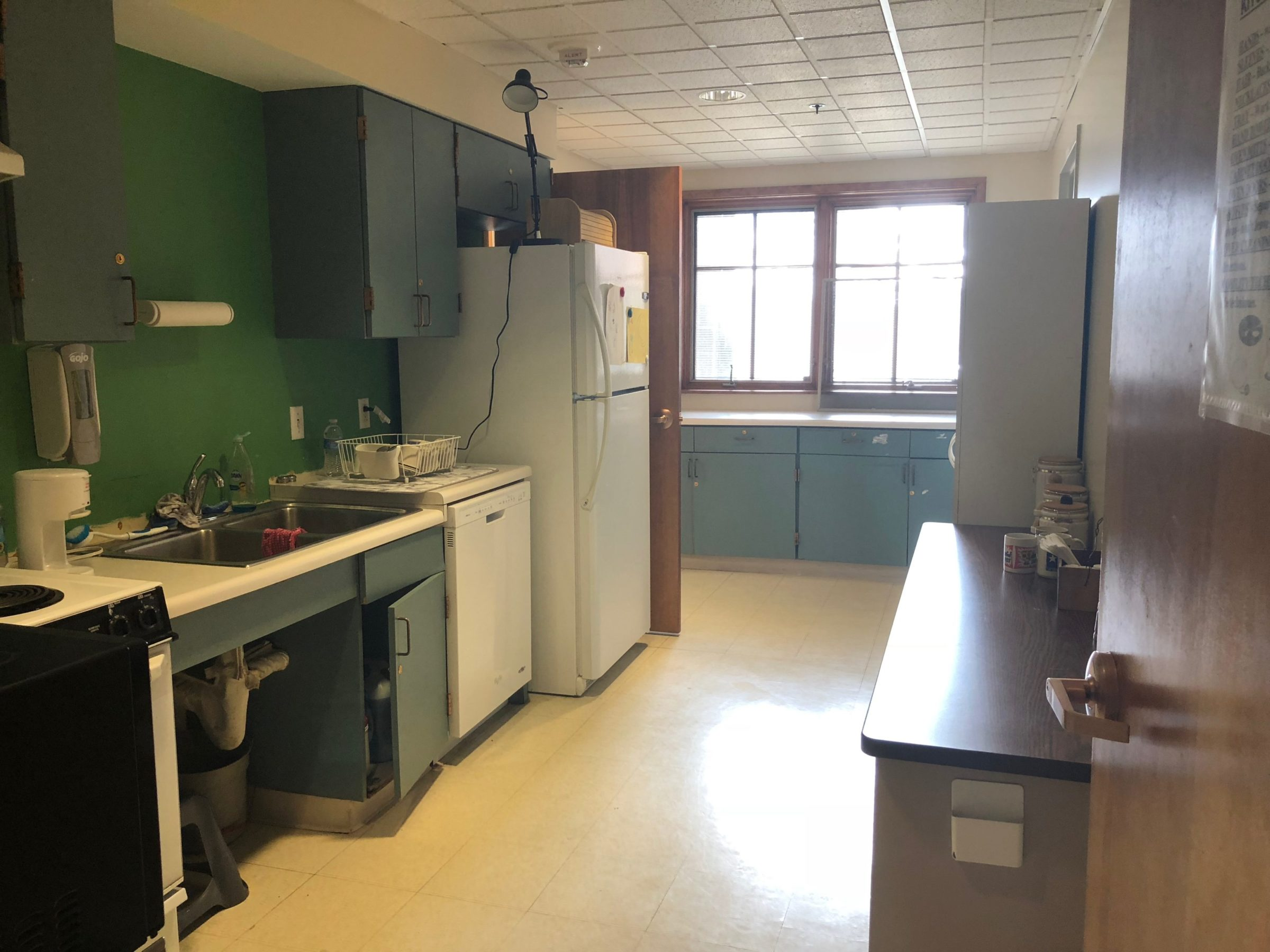 Stove, Sink, Cabinet and Fridge on green wall. Window in the background with light shining into space.