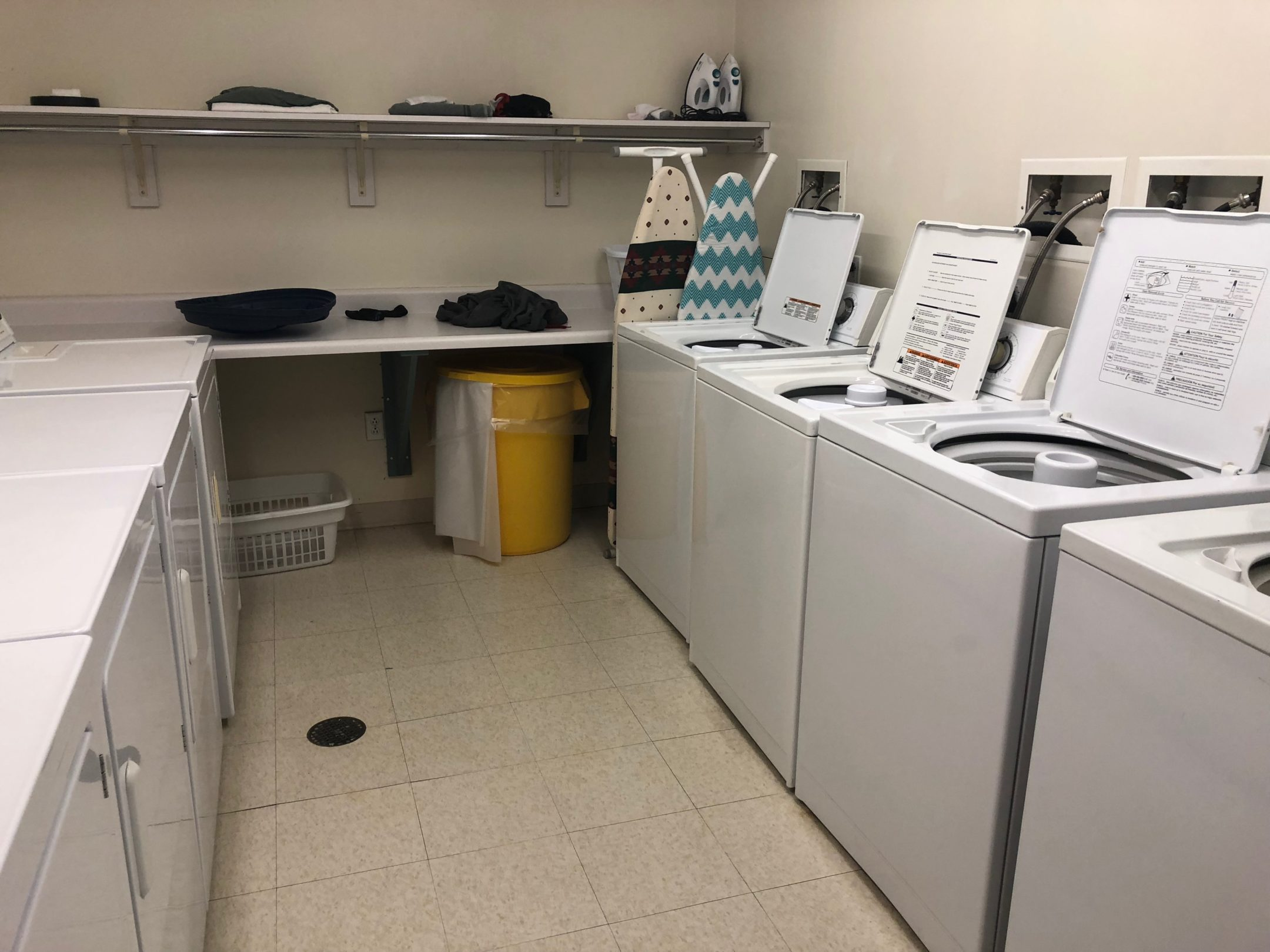 Wall along right has 4 white washing machines with lids open. Left side is 4 dryers. Back wall is table for folding clothes and 2 ironing boards. A rack with a shelf for storage and a rod for hanging clothes.