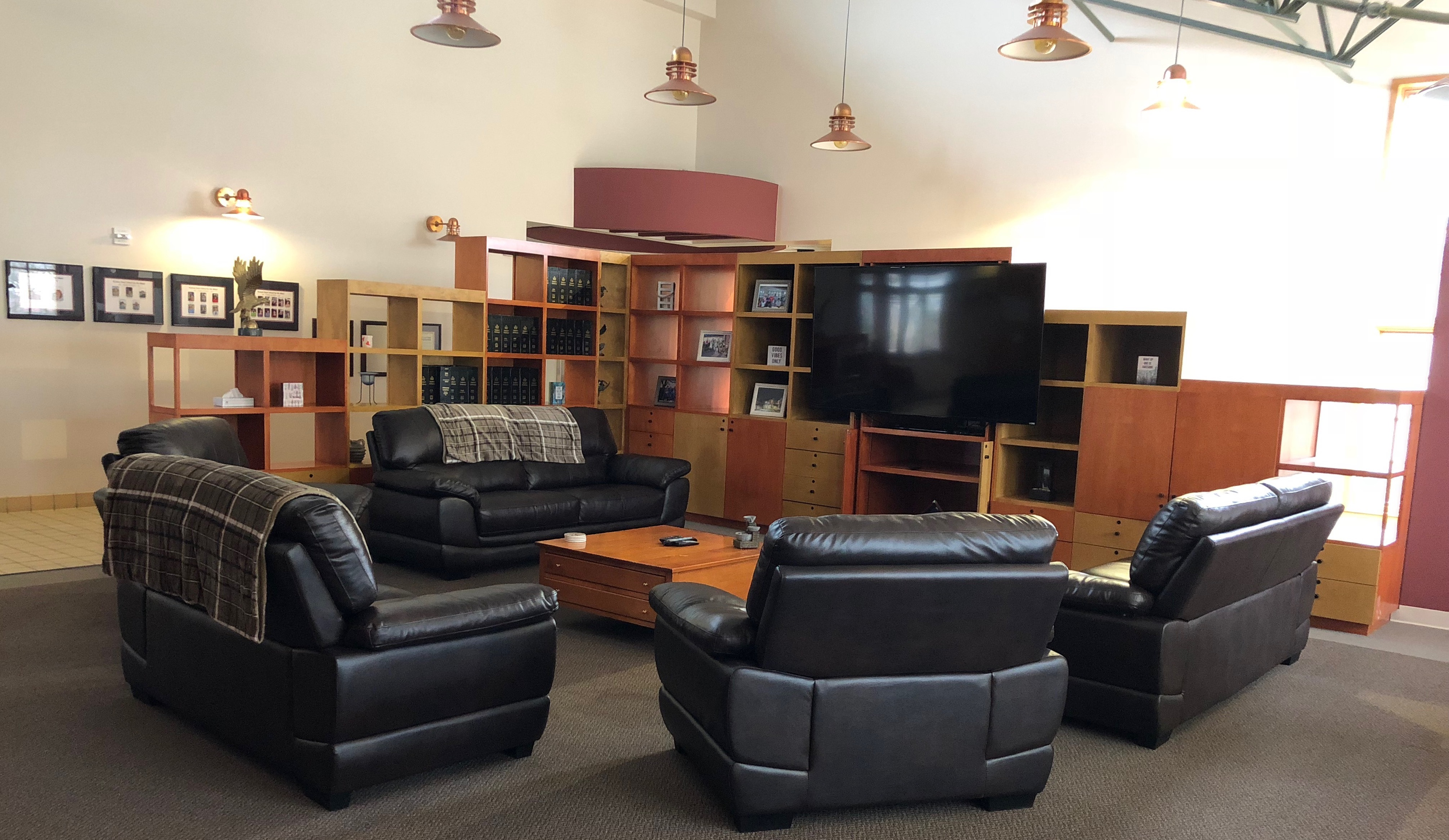 A large lounge with five 2 seat sectional recliners forming a circle. A large square coffee table in the center. A partial wall beyond containing a Large Screen TV, books and stereo system. The Partial Wall is formed by 2 stair stepped shelves - wall units that meet to form a corner. The Large Screen TV to the right and books to the left.