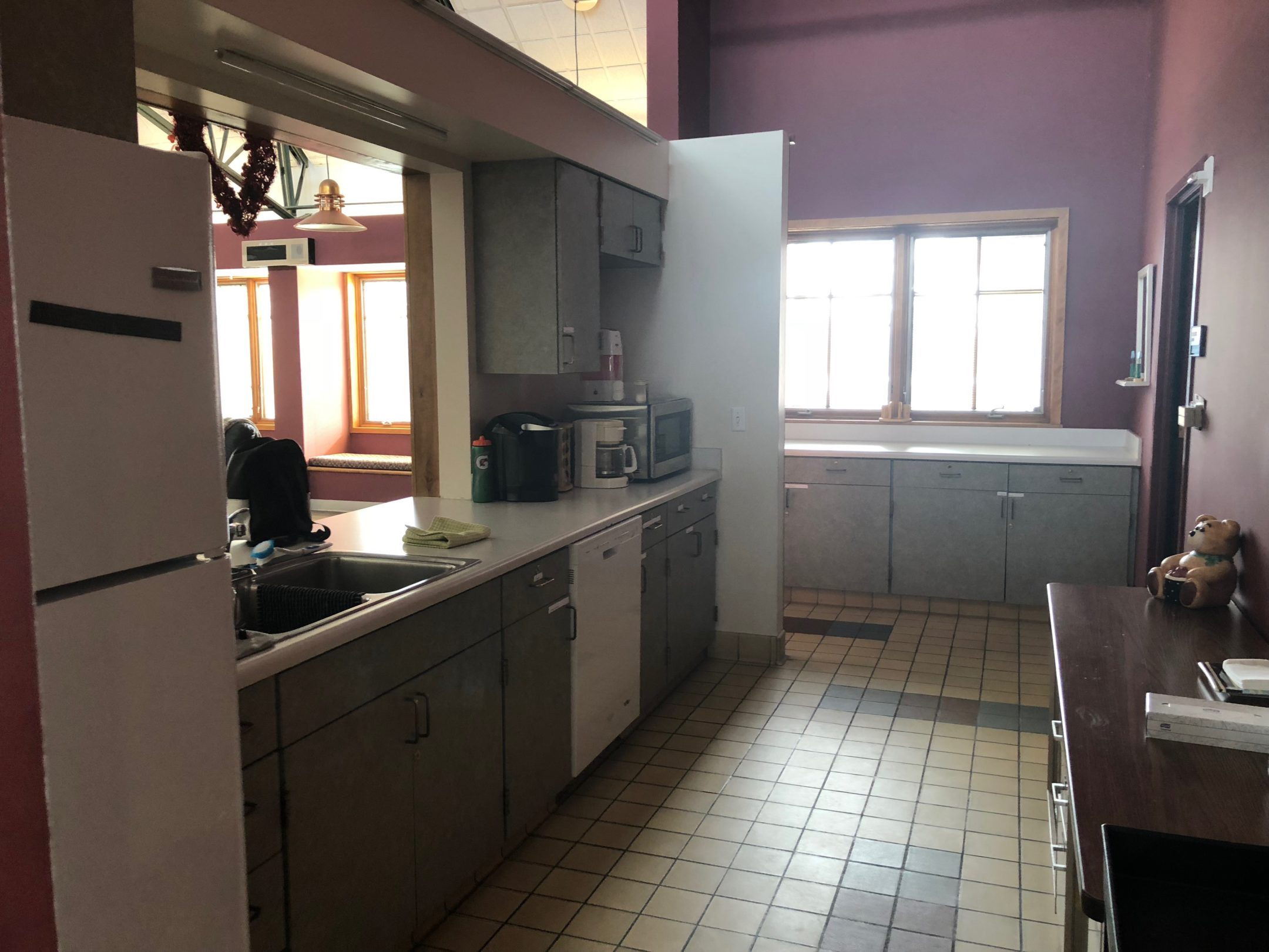 Left side is a Fridge, a sink, dishwasher and cabinets. A large opening in the wall above the kitchen looks out to the upper level lounge.