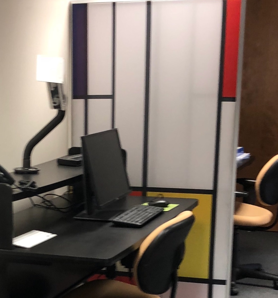 A two tiered desk with a computer on first tier and monitor arm on the second tier. A 5'x3' created with white, red and yellow squares plexiglass framed in by navy stripes creates a screen placed between two desks.