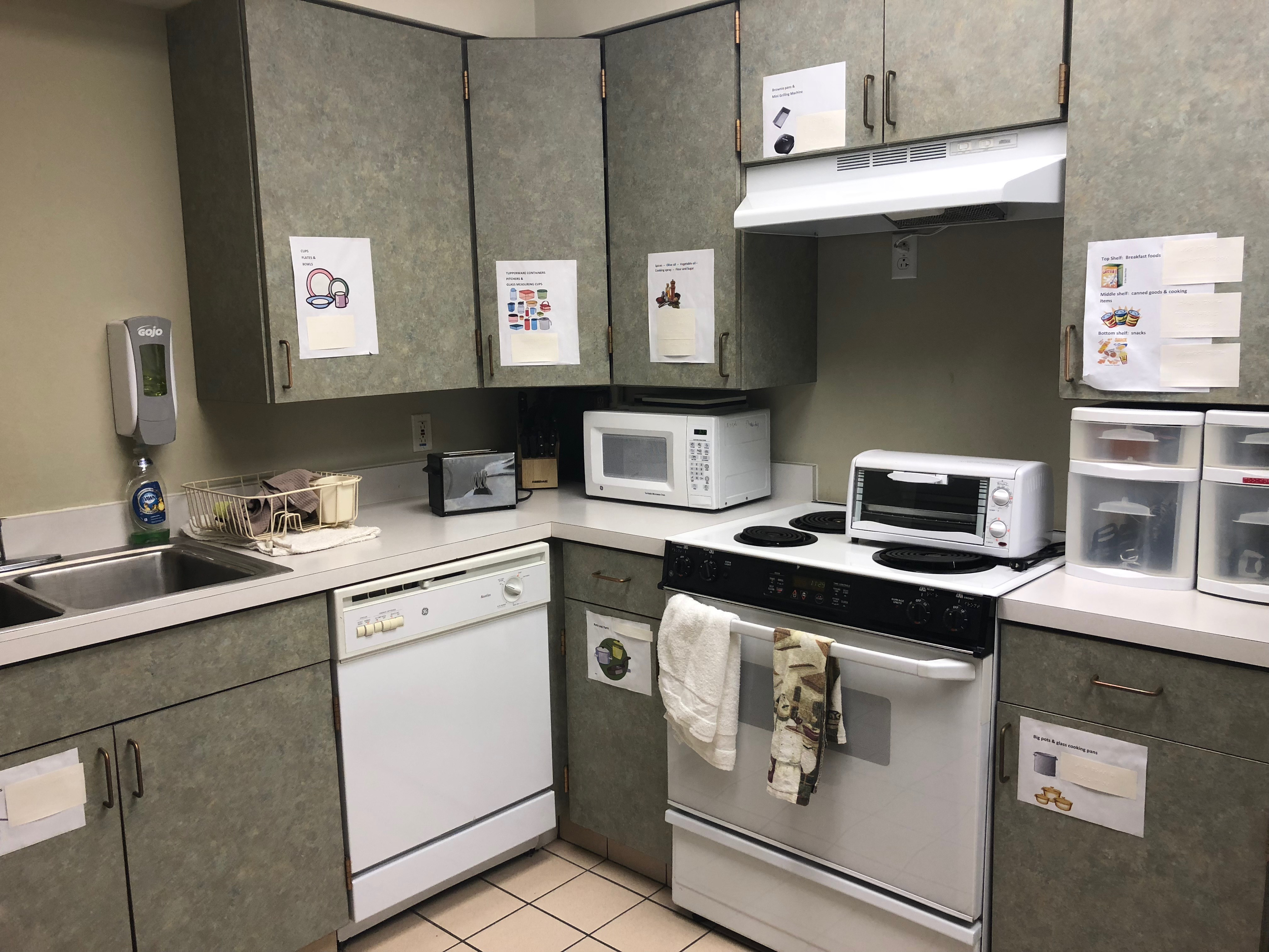Apt kitchen with green cabinets on wall and floor. A sink, white dishwasher, oven/store, microwave and toaster oven. Beige tile floor and walls.