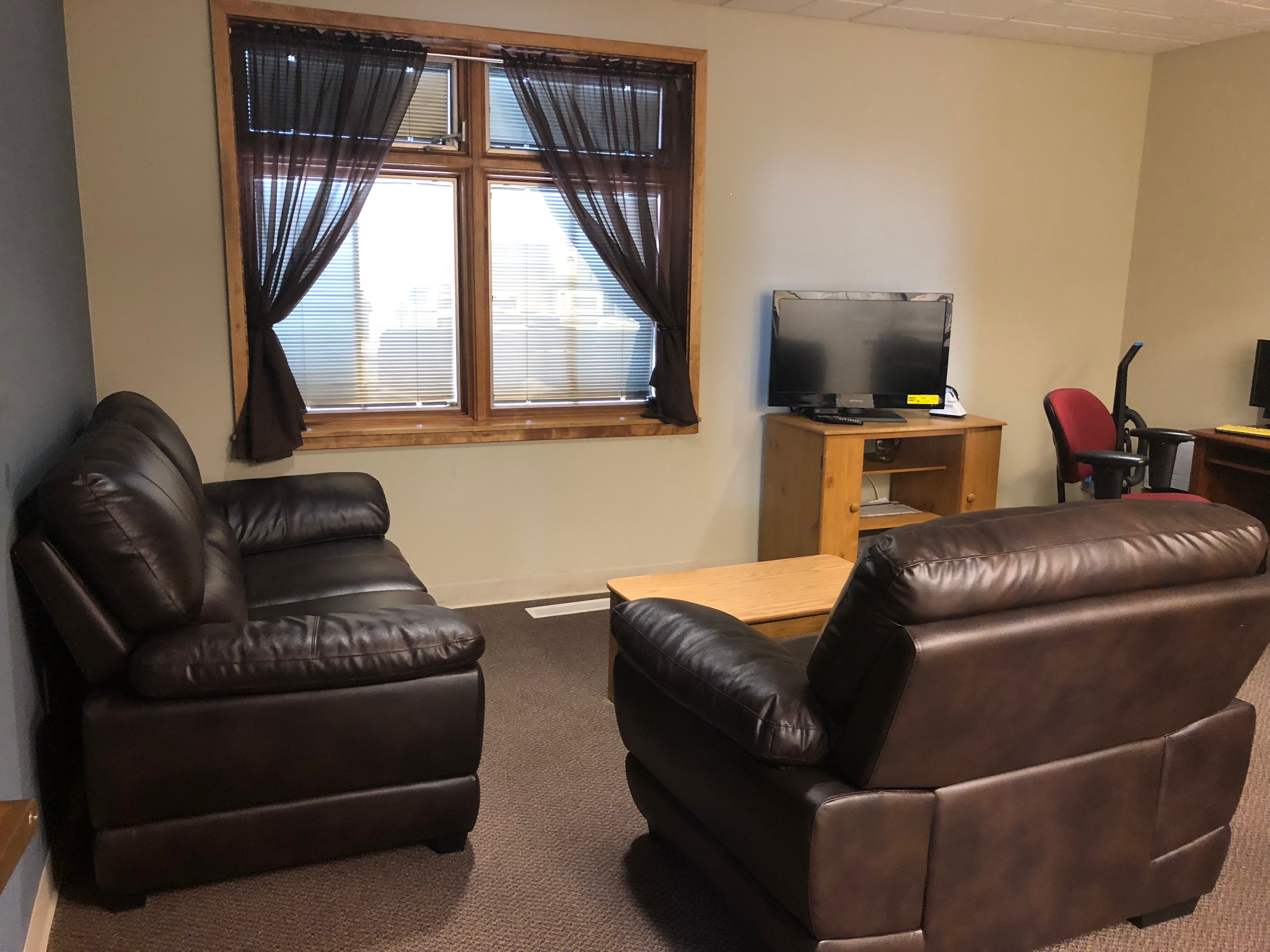 Living area containing a leather loveseat and recliner with a coffee table on the floor in front of them. The recliner is facing a window with green curtains. To the right of the window is a stand with a TV.