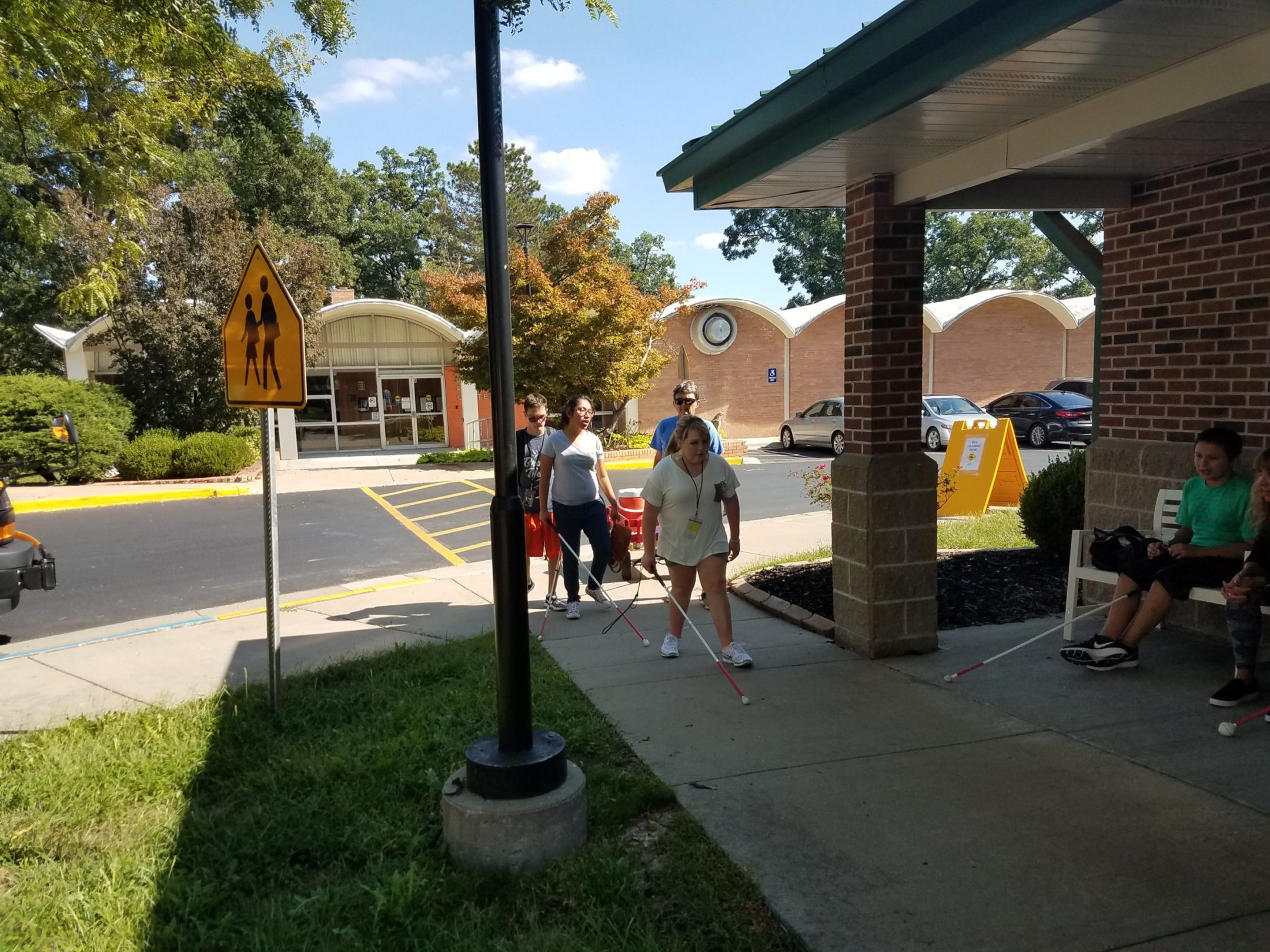 Three students arriving on campus. The recreation center in background, yellow crosswalk and then sidewalk to the back door of Edlund Hall. 2 students sitting on chairs outside the cottage as students walk by.