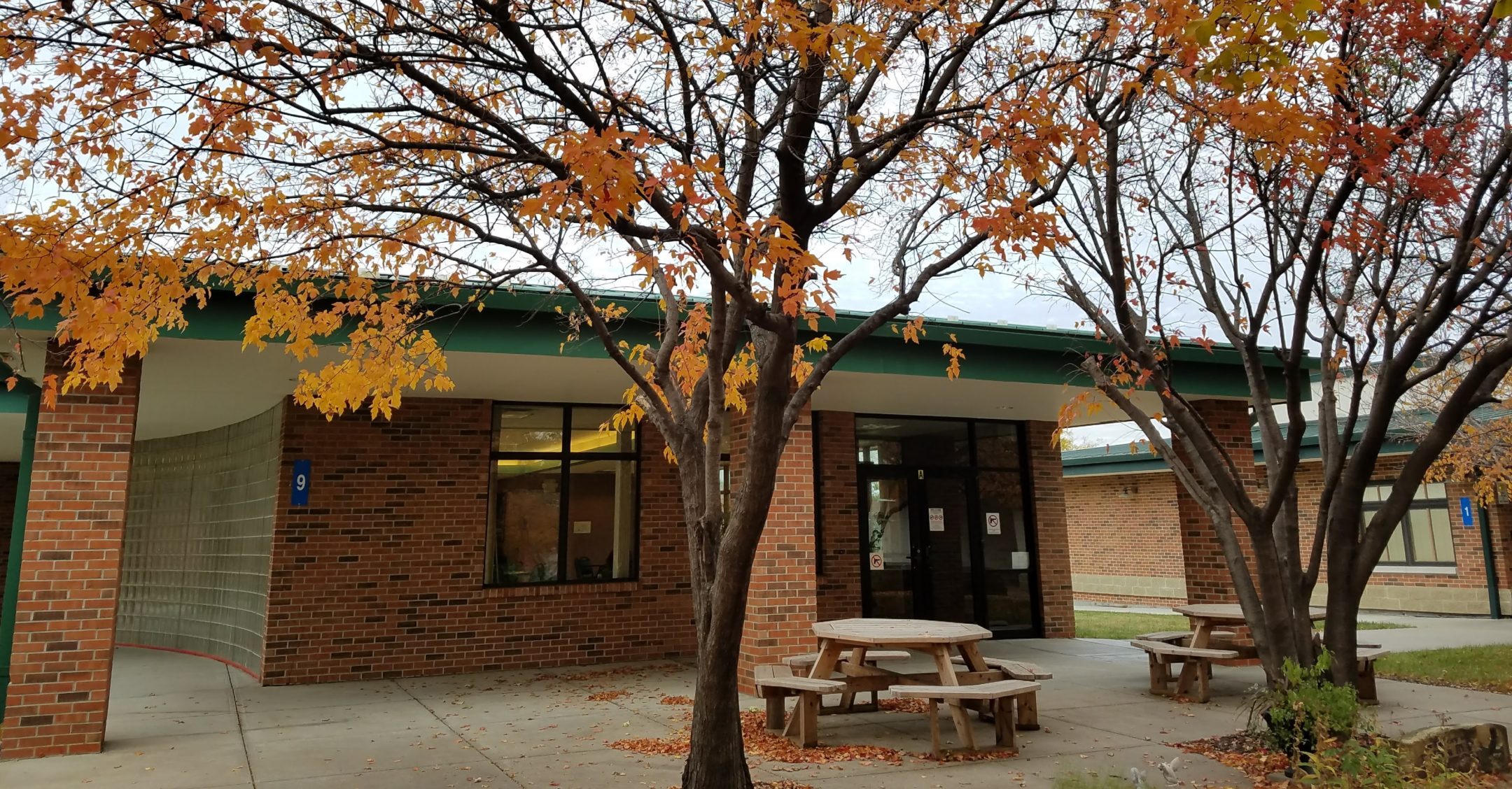 Entrance to cafeteria building showing glass opaque brick wall on the left, red brick wall with large window and a large automatic door on front facing wall. Three brick pillars and large concrete patio with two round picnic tables out front. Three large trees with leaves in fall colors out front.