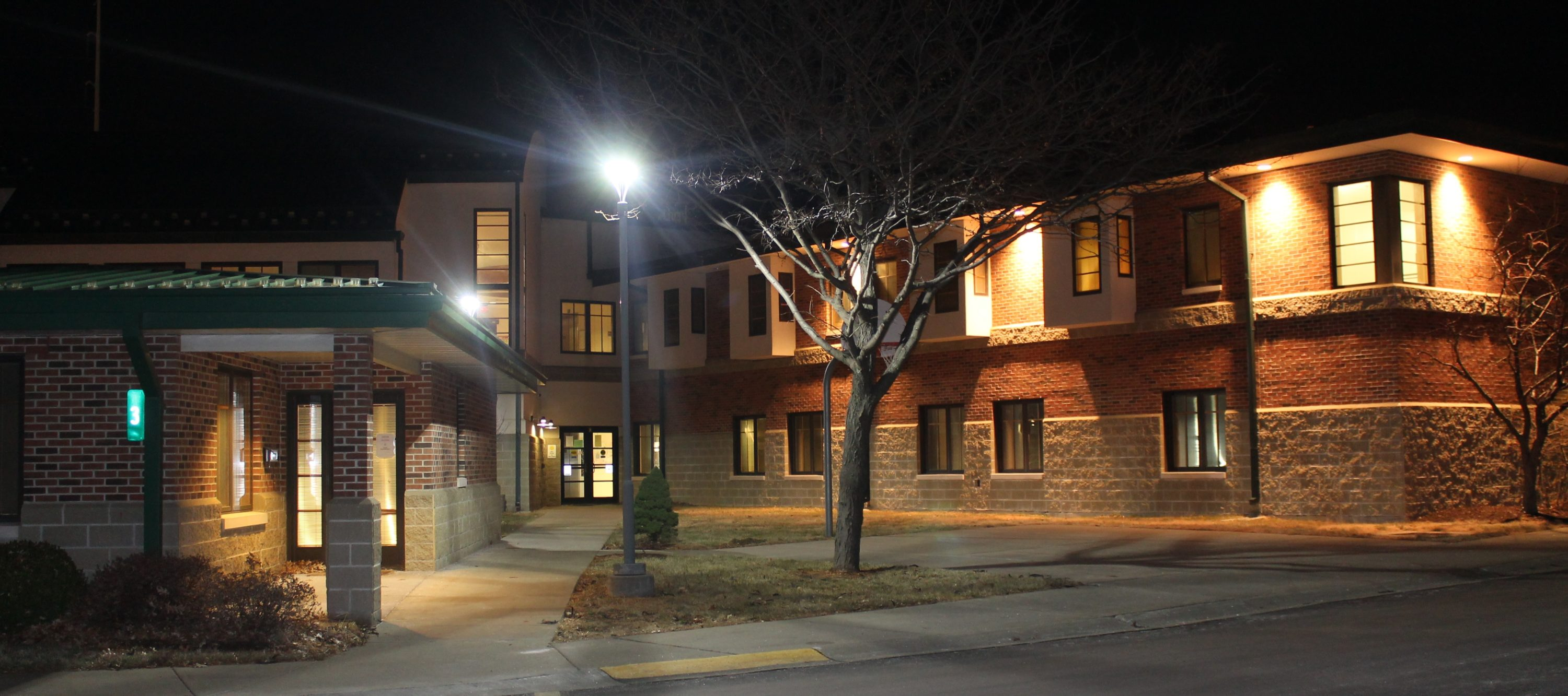 Residence Hall at Night. A large 2 story building with 2 trees and a light pole in front. Light from windows and outdoor lighting shine in the darkness.