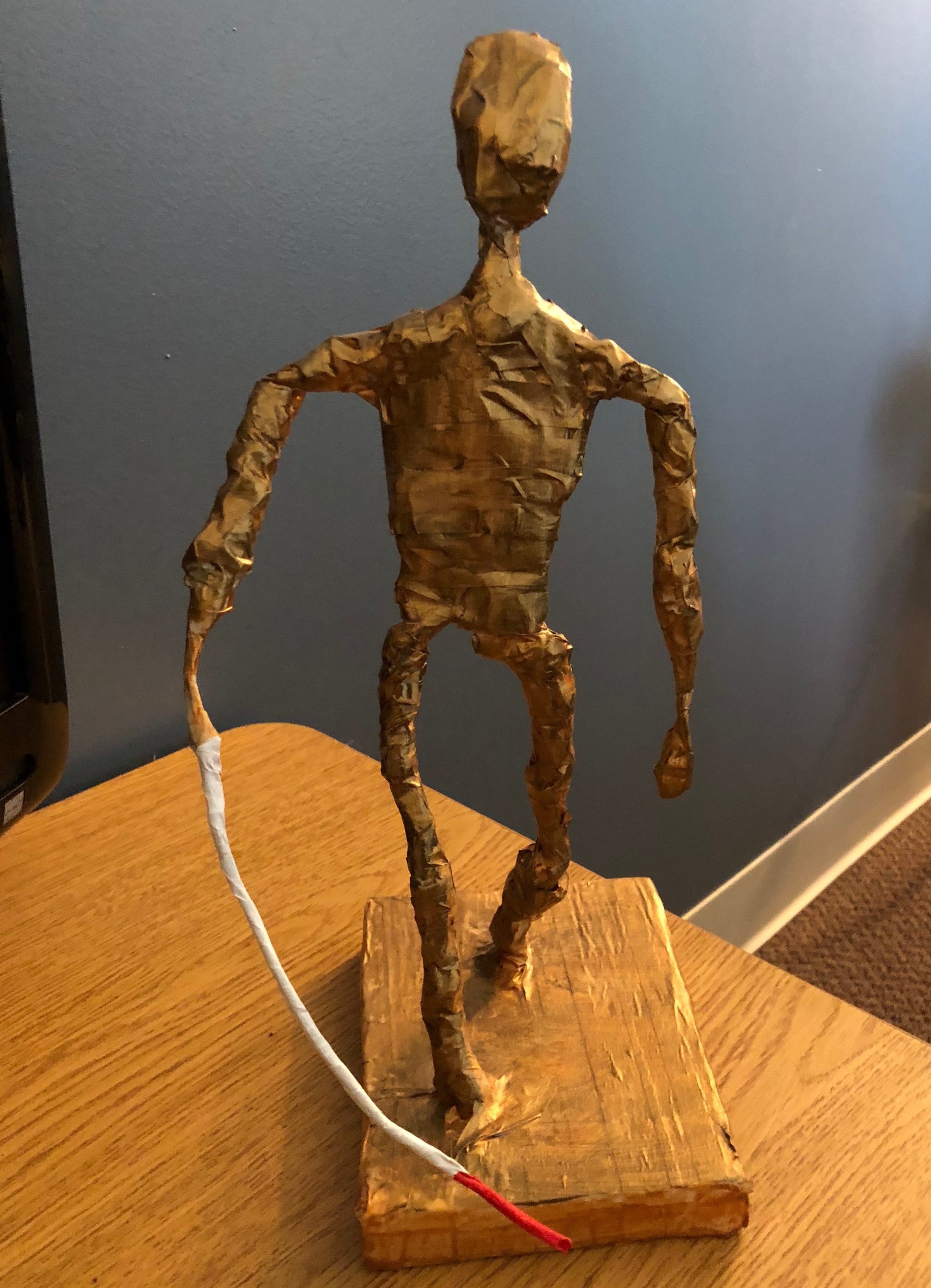 a thin paper mache sculpture painted in gold, using a cane.