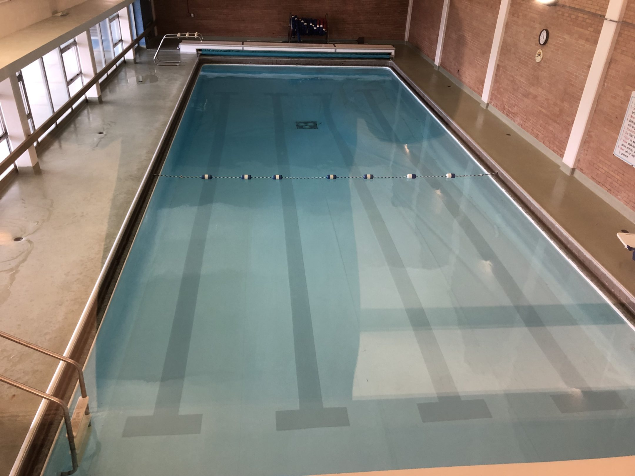 overhead picture swimming pool with a set of benches on the far end and metal steps on the left.