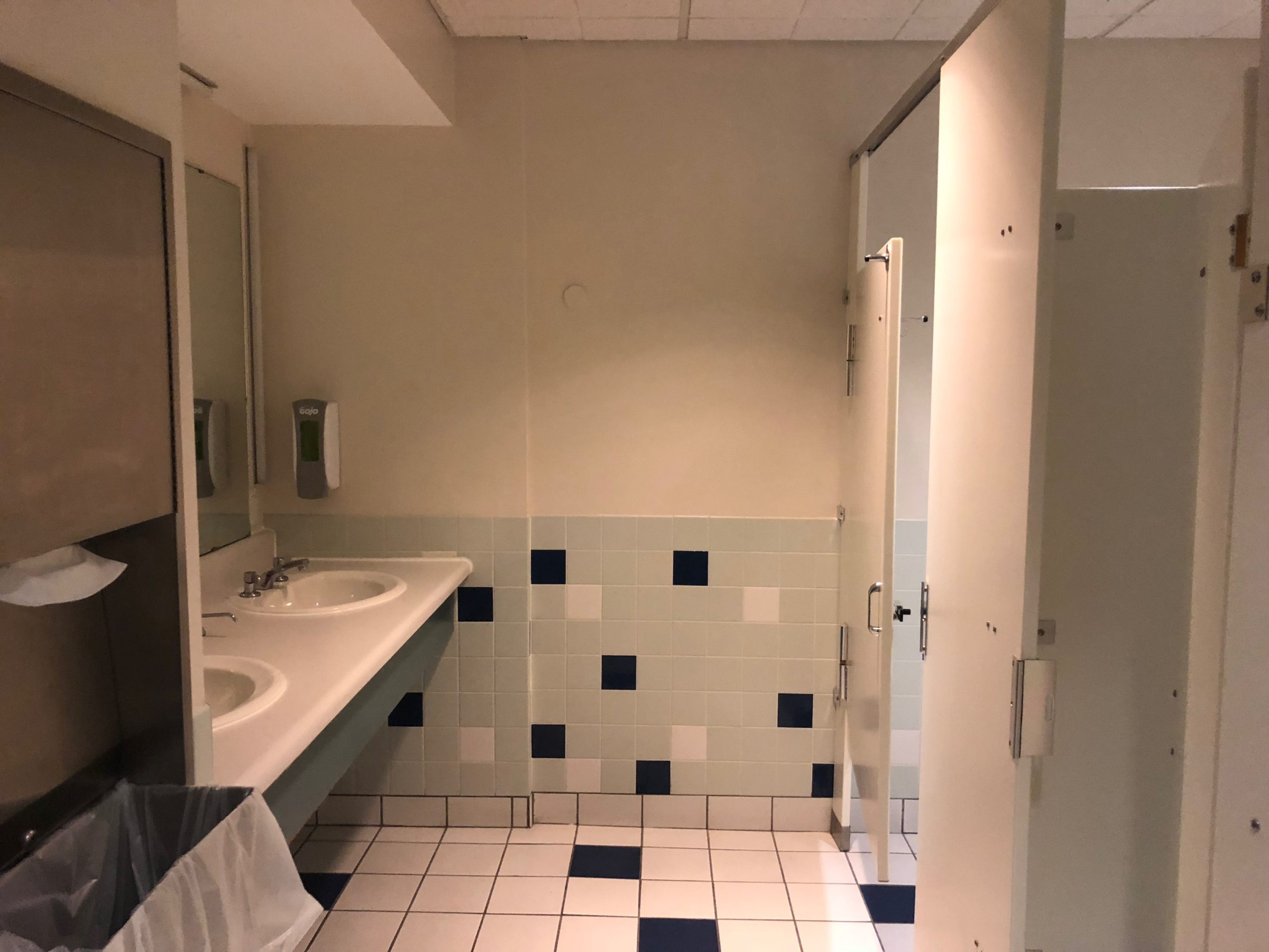 Restroom with 2 sinks and large mirror along the left side and 4 bathroom stalls along the right side. The floor is white tile with blue tile accent. The wall is tiled halfway up with light green tiles interspersed with navy and white tiles.