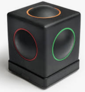 A black square plastic box with a raised circle on top and 4 sides. Each circle is outline with a different color: orange, red and green are seen in the photo.