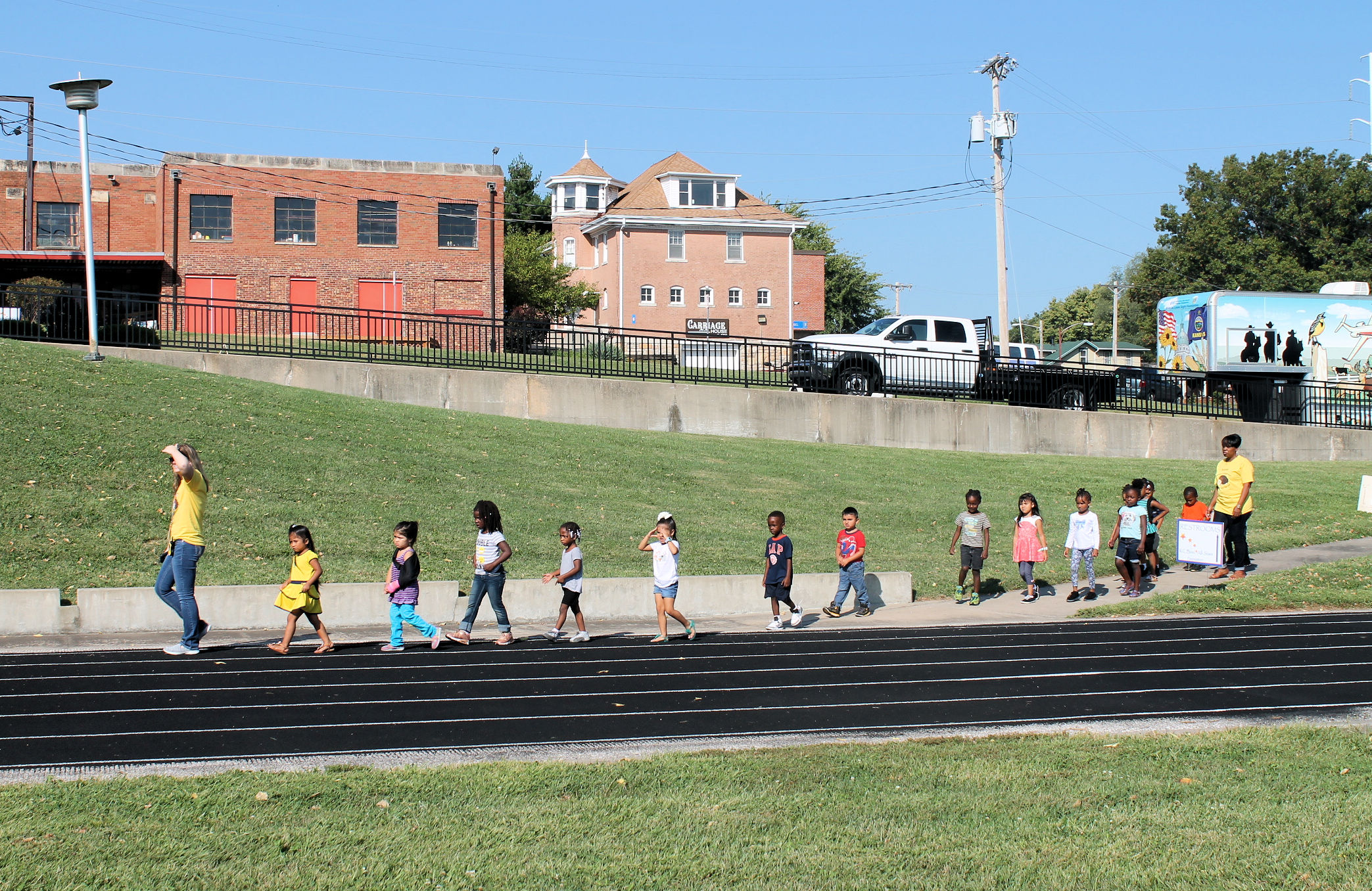 A group of young children following a leader onto the KSSB track for the All Star Walk.