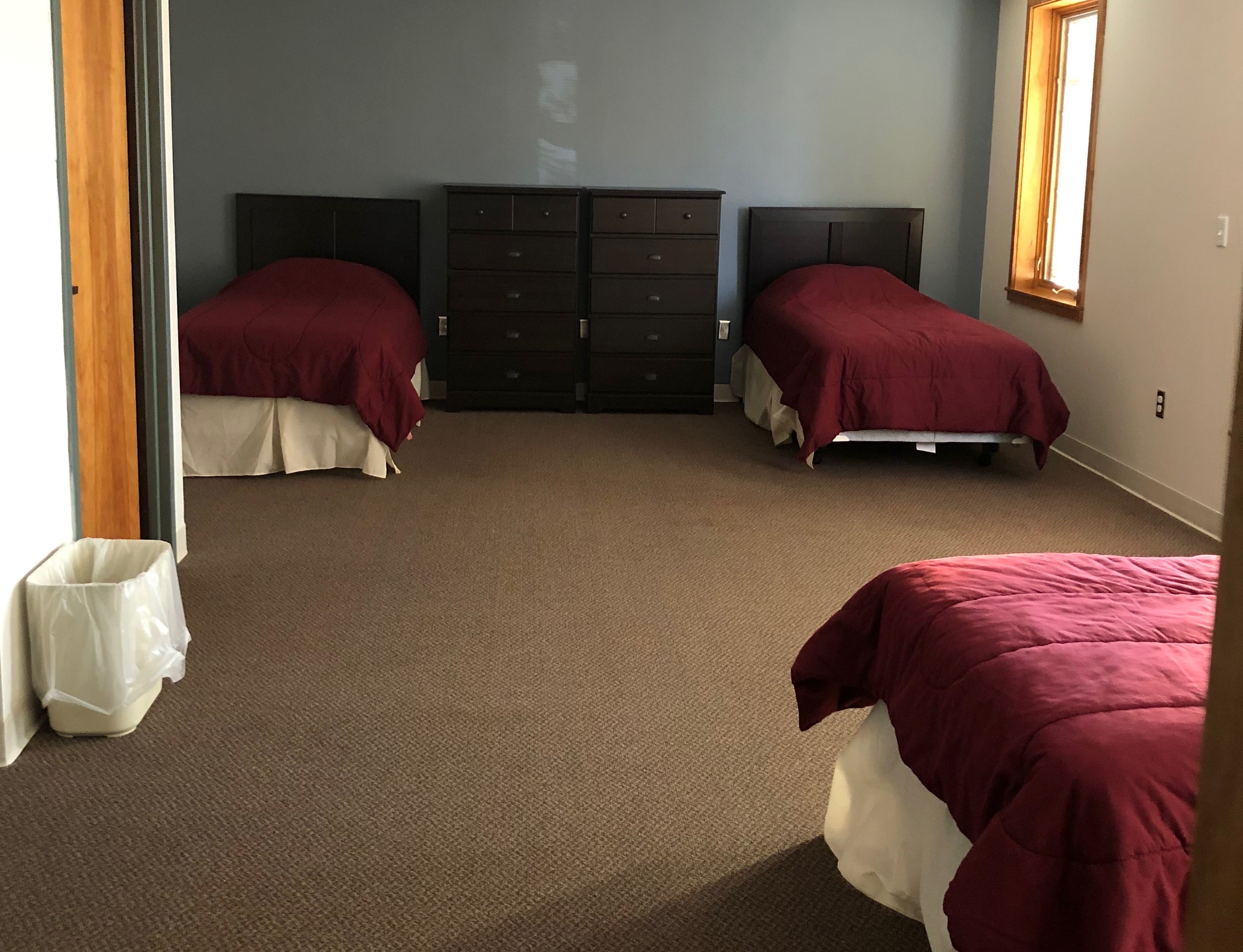 A dorm room with triple occupancy. Two beds with headboard agains one wall and two 5 drawer dressers between them. The third bed set on other side of the room with headboard against the opposite wall.