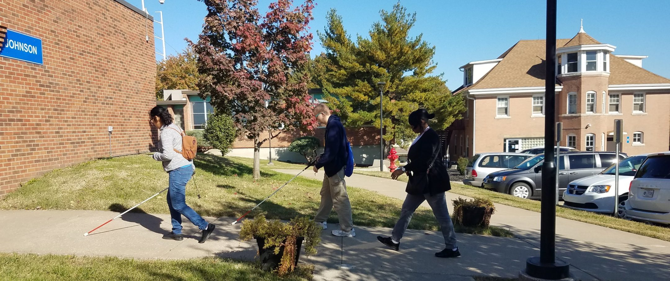 Three students walking on sidewalk with canes out front as they enter the Johnson Building. First female student wearing jeans and white shirt. The next two are males wearing coat jacket and kaki pants.