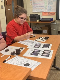 Student sitting at a table with pens and papers of images of the phases of the moon.