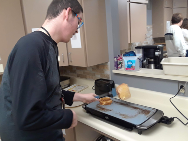 Students using a spatula to toast a ham and cheese sandwich.