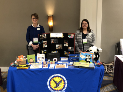Field Service Early Childhood Specialists standing in front of a table a blue table cloth and KSSB Logo. Books and equipment on display on the table.
