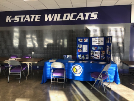 A KSSB Display table at Kansas State and the words K-State Wildcats on the wall above the Table Display.