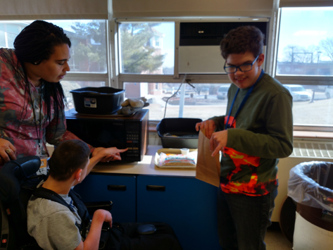 Student sitting in his wheelchair being assisted hand under hand to open a microwave, along with another student standing next to them holding a paper bag and smiling.