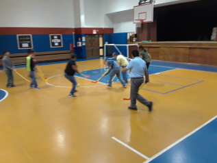 Students holding sticks and playing field hockey in the gym.
