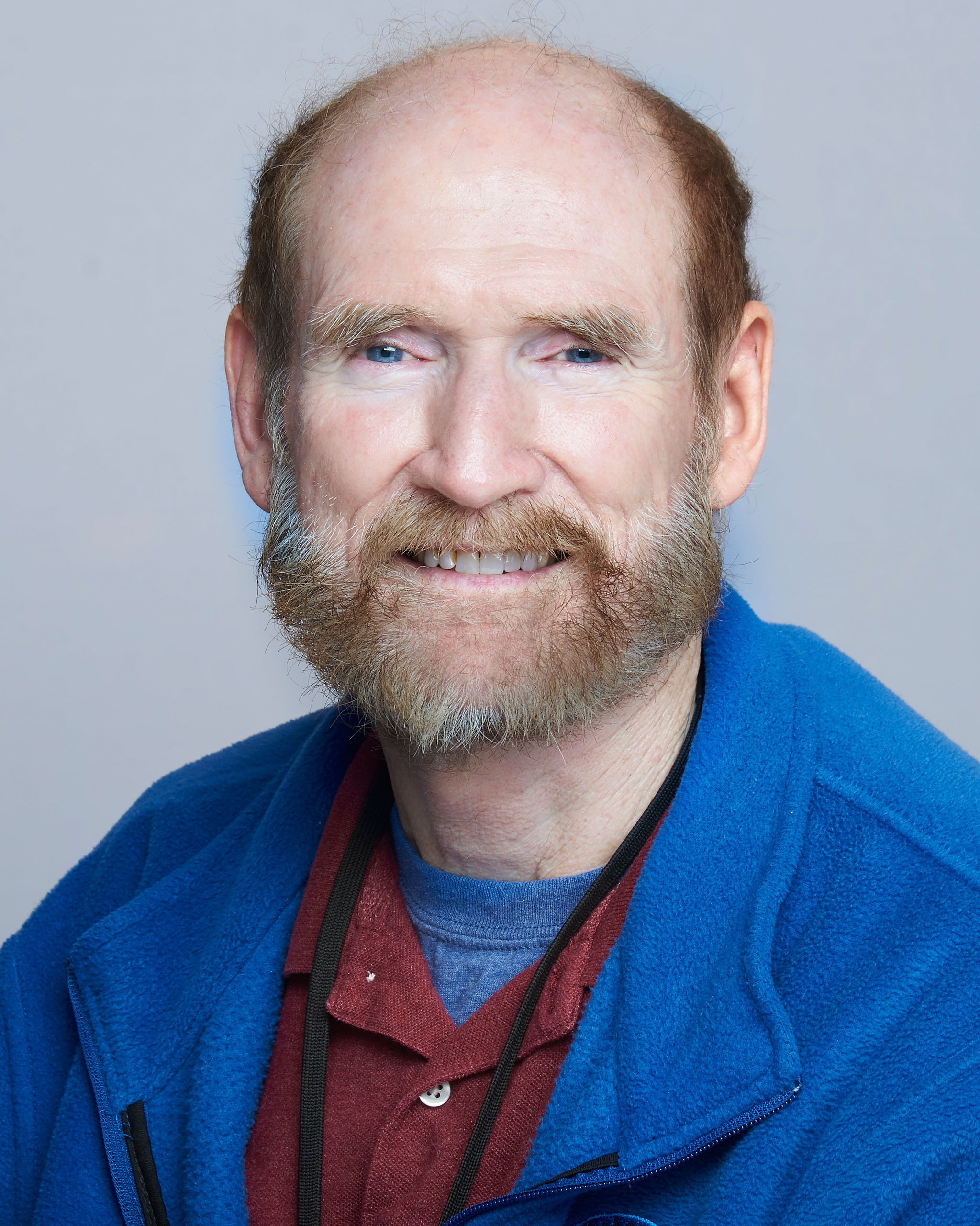 Bob Taylor wearing a maroon shirt and a blue jacket.