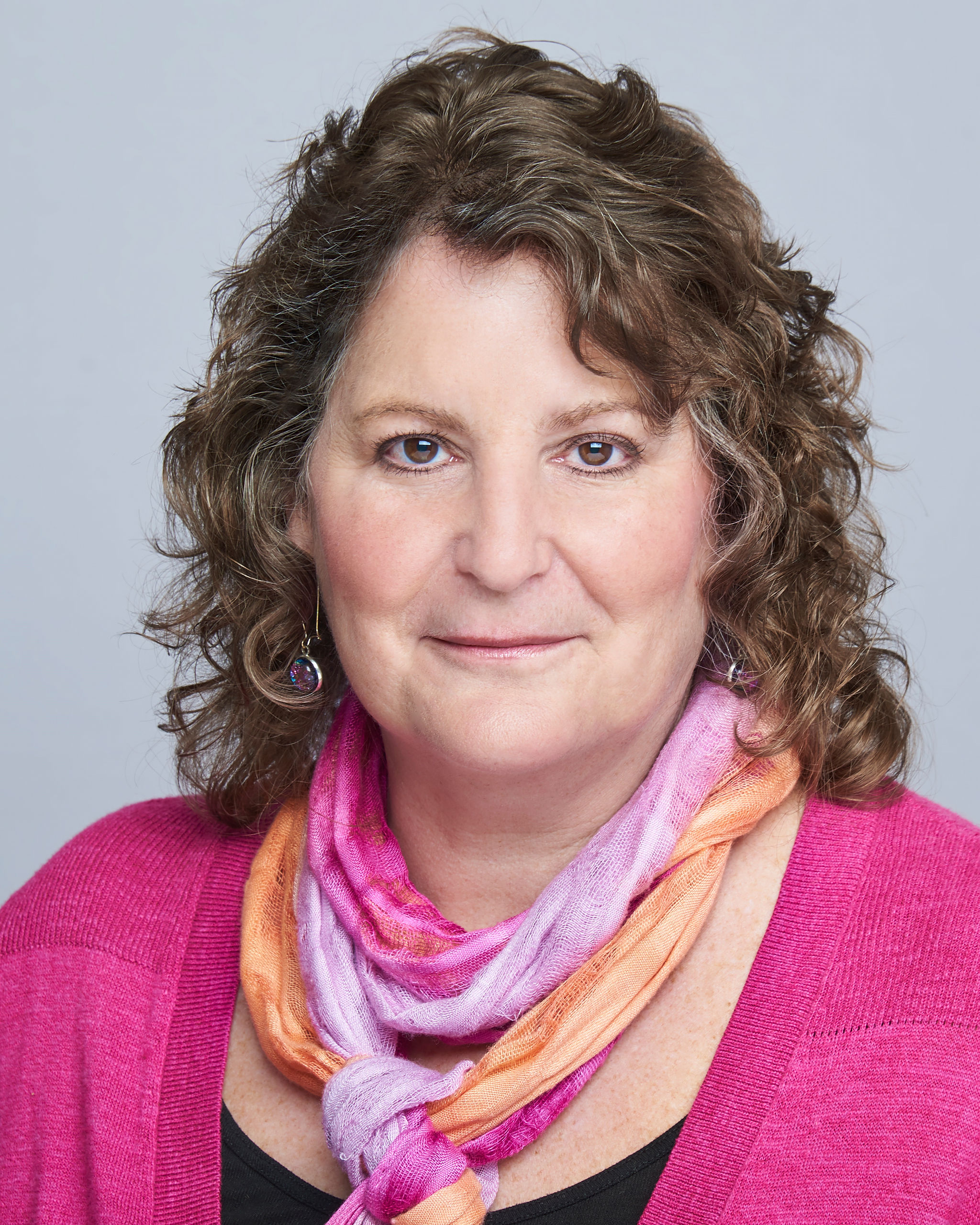 Judy Imber wearing a pink sweater over a black shirt. A pink and orange scarf.