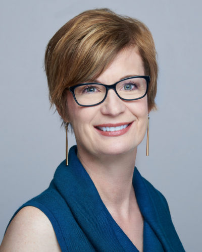 Susan Threinen wearing a dark blue short sleeve collared shirt.