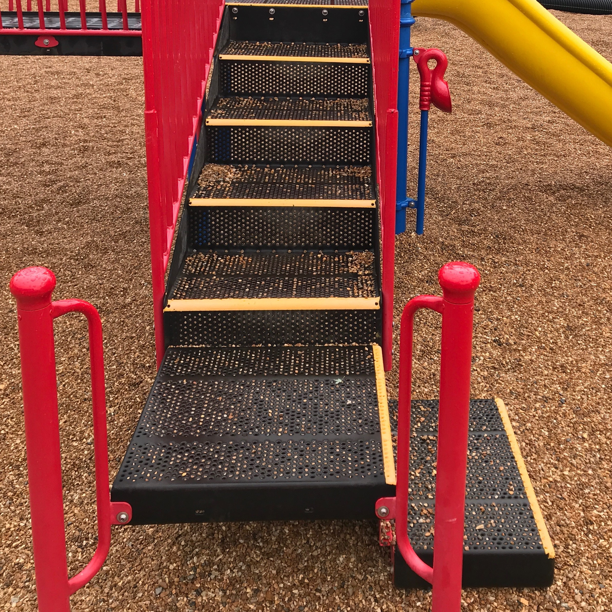 Playground jungle gym with stair edges painted in yellow. The railings and bars in bold red or blue.