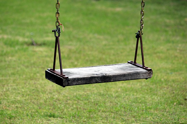Wood swing seat connected to metal chain link above grassy ground.
