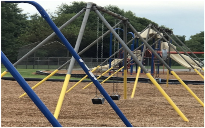 Two swing sets sitting side by side. The foreground swing set poles are painted in bold blue. The silver poles of the swing set in background is painted with bright yellow half way up each pole to increase visual contrast.