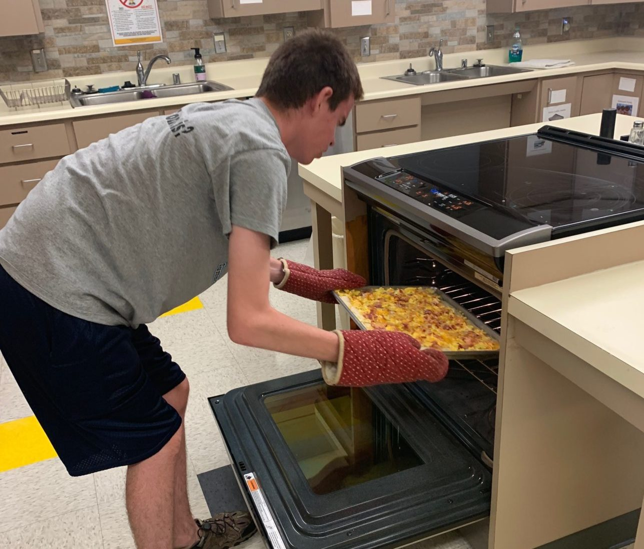Student putting tray in the oven.