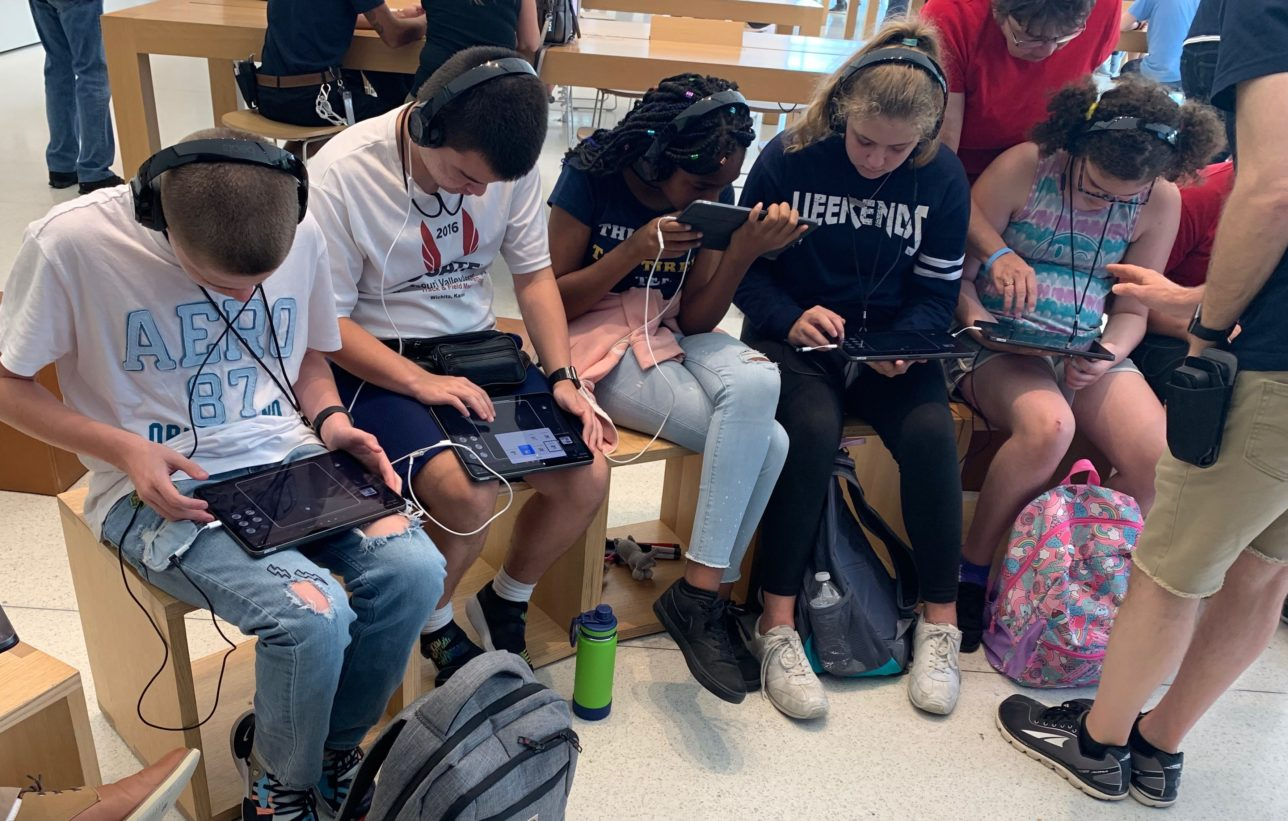 Students using headphones and iPads in apple store.