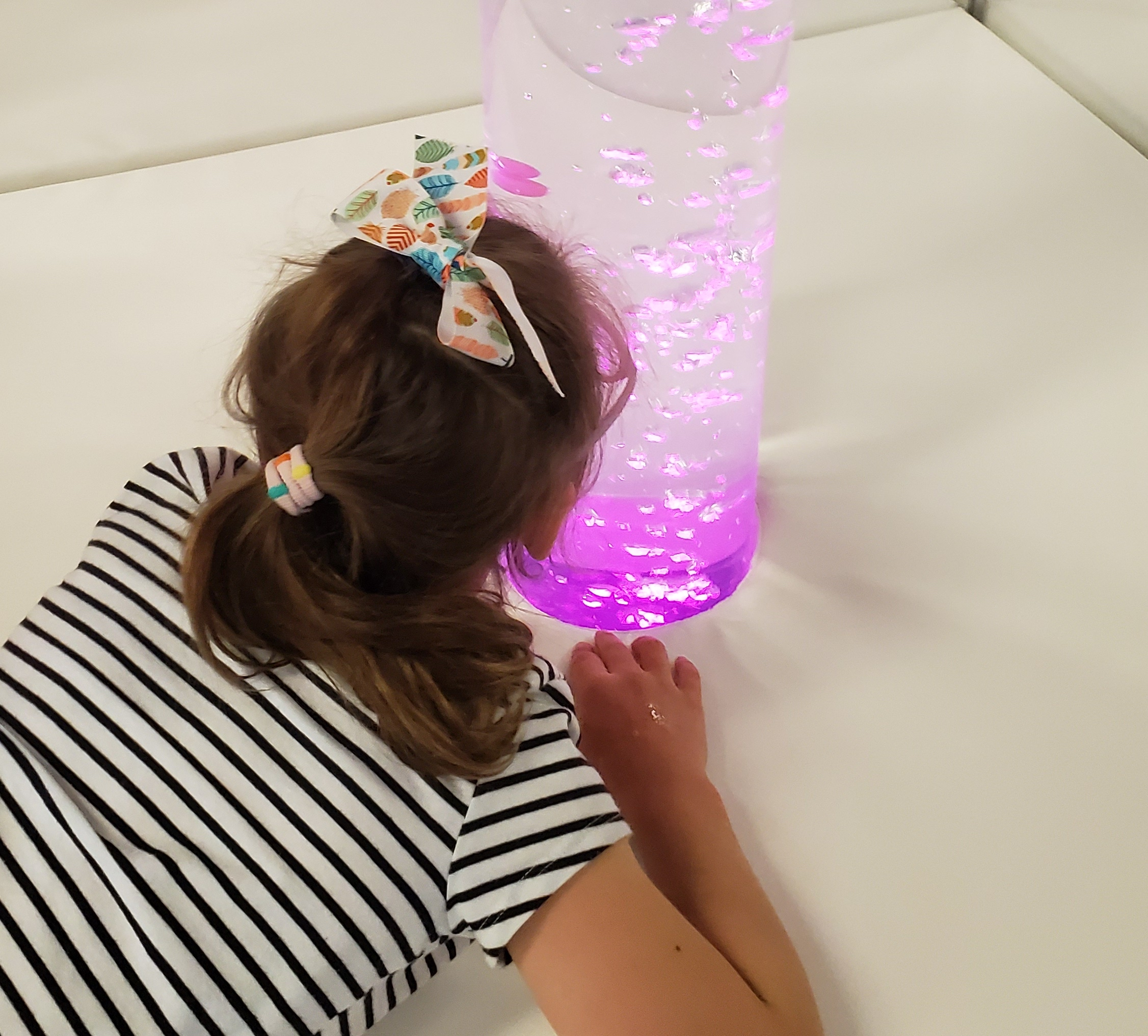 Child looking at tall tube with pink bubbles.