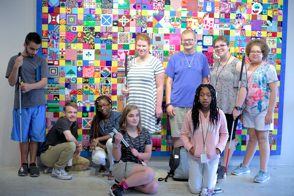 Students standing or sitting in front of a large 10' by 13' brightly colored beaded quilt.