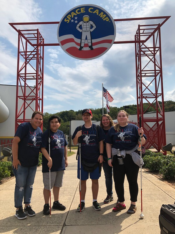 Two teachers and three students wearing spacecamp shirts and holding their canes are standing under the entrance to Space Camp.