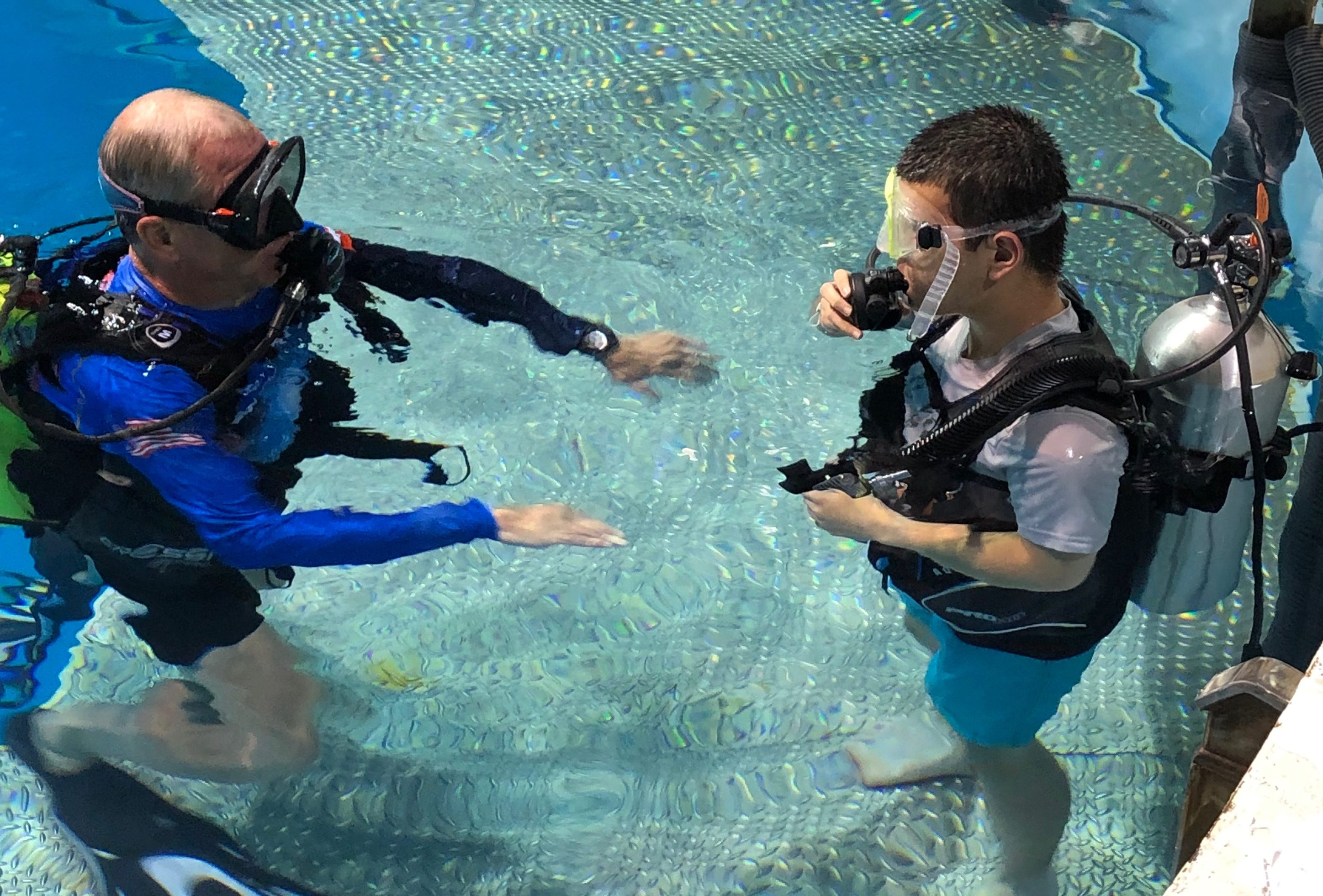Rich standing in water, wearing scuba gear and listening to an instructor provide directions.