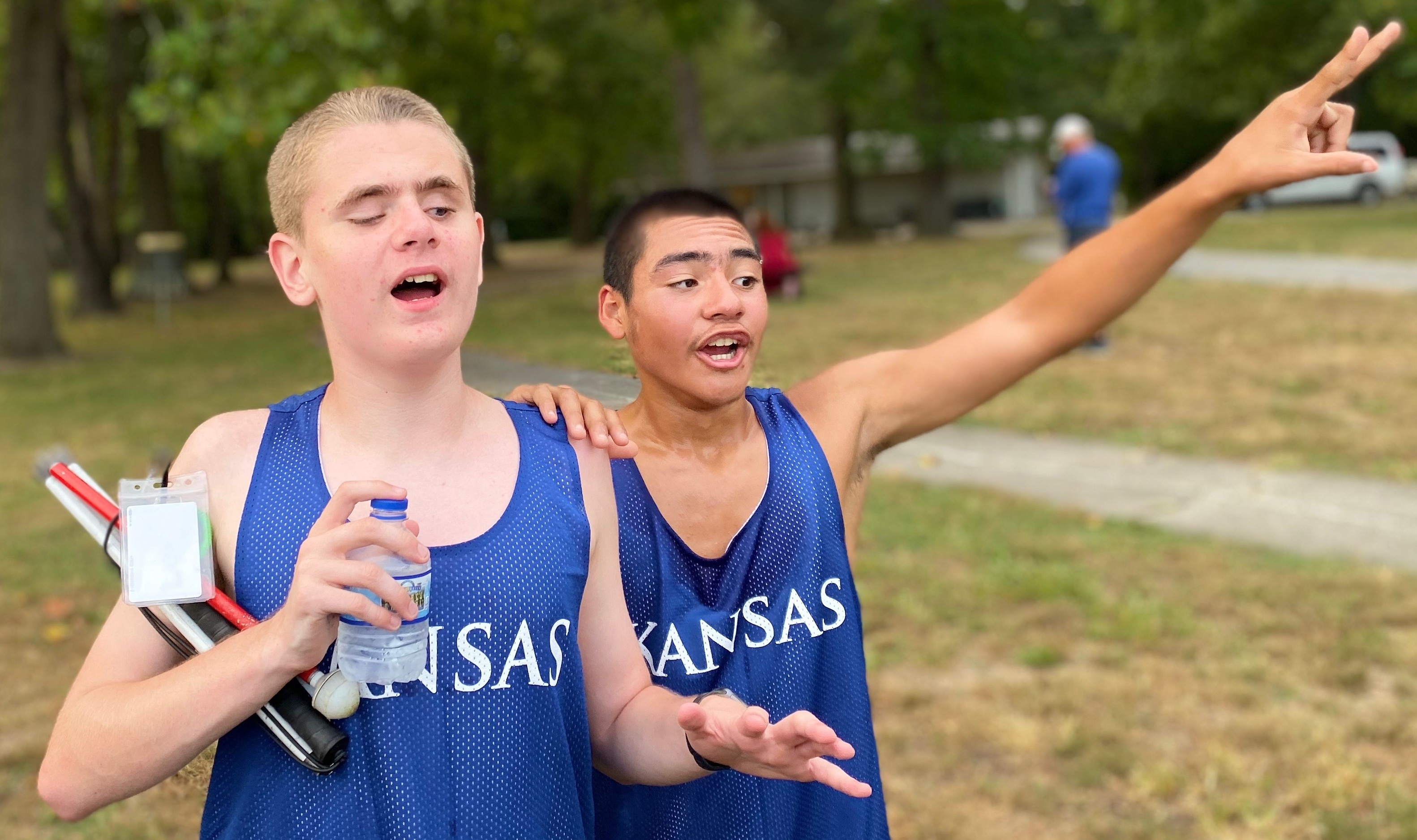 Two Male Students In Track Uniforms. One Holding Cane And Water Bottle, The Other Has Hand On Teammates Shoulder And Oner Hand Raised To The Sky.