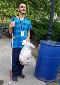 Student with a trash bag full of garbage found at the park.