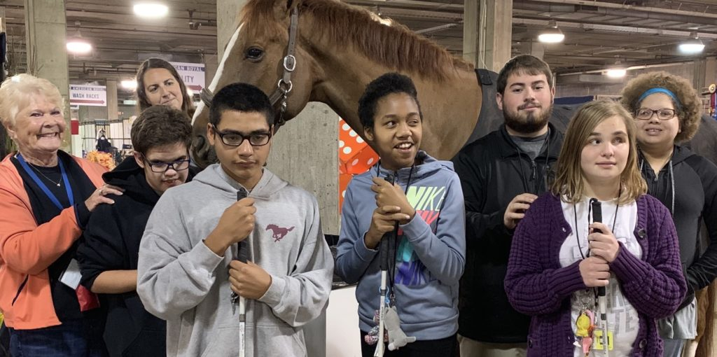 Students standing in front of a large horse.