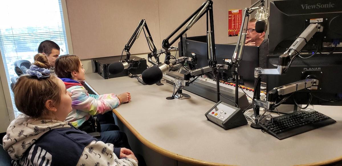 Three students visiting a radio station.