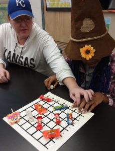 A teacher and student finding candy on a coordinated grid.