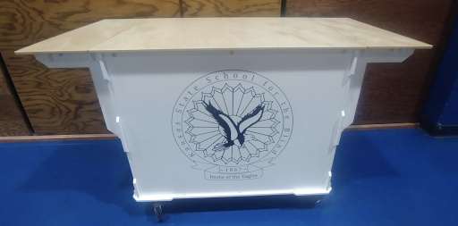 "Coffee Cart with wood top and white base with the KSSB logo painted in black. The logo is a circle with a flying eagle in the center. It reads: ""Kansas State School for the Blind, 1867. Home of the Eagles."""