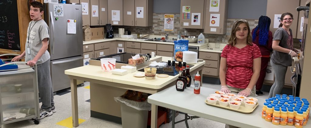 Student in kitchen ready for the pancake breakfast customers.