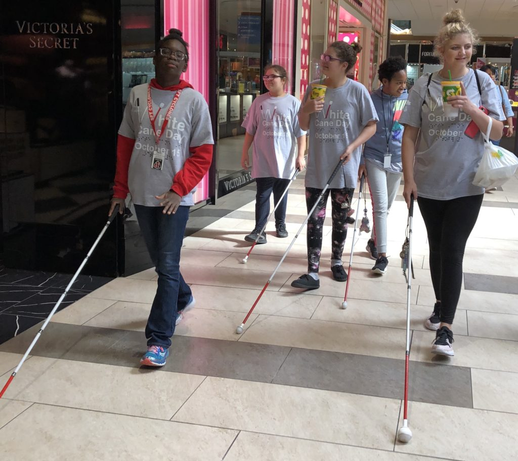 Students walking in the mall with their canes.