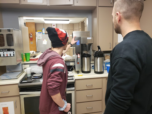A student in the kitchen, wearing hat, and demonstrating the coffee machine to a visitor.