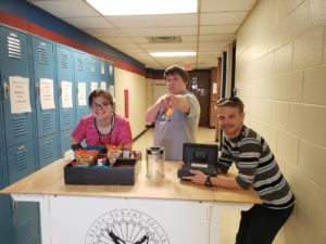 3 Students Standing At The Coffee Cart - One On The Left, Leaning Over The Snack Basket. A Second Student Behind The Cart Pointing At The Camera. A Third Student With Elbows On Cart Holding The Cash Box.