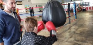 Student wearing red boxing gloves and punching a bag hanging from the ceiling. A boxing coach is standing near and smiling.