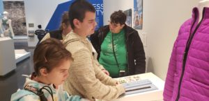 Student standing in front of an exhibit with adapted zippers for a jacket.