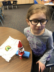Student sitting at a table with a fortune cookie and an Elf in red sitting on a blue speaker box.