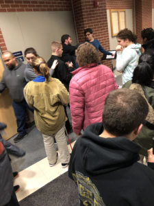 Students standing around visiting. A friend pats jazz player on the back.
