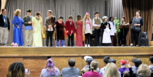 Students in costume standing on the stage with audience watching.